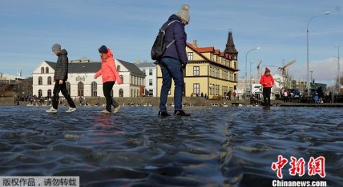 寒潮来袭冰岛首都池塘结冰,民众撒欢玩水上漂